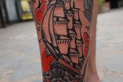 inferno-tattoo-barcelona-old-school-fernando-morano-mediano-pierna-barco-velero-rosas-rojo-negro