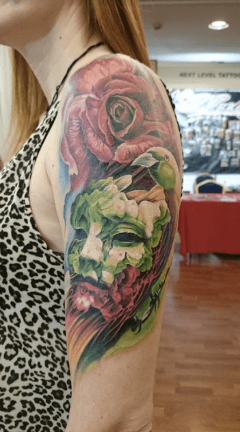 Realismo color, Christian Kurt Bieber. Tatuaje grande en brazo de máscara, flores y pájaro.