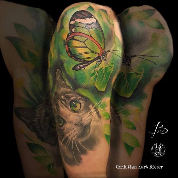 Realismo color, Christian Kurt Bieber. Tatuaje grande en hombro y brazo de gato y mariposa.