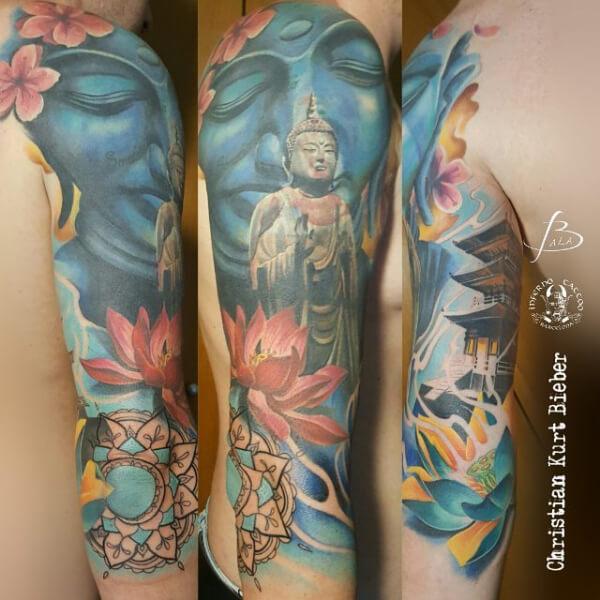 Hindú y mandalas, Christian Kurt Bieber. Tatuaje grande en brazo de pagoda, buddha y flores.
