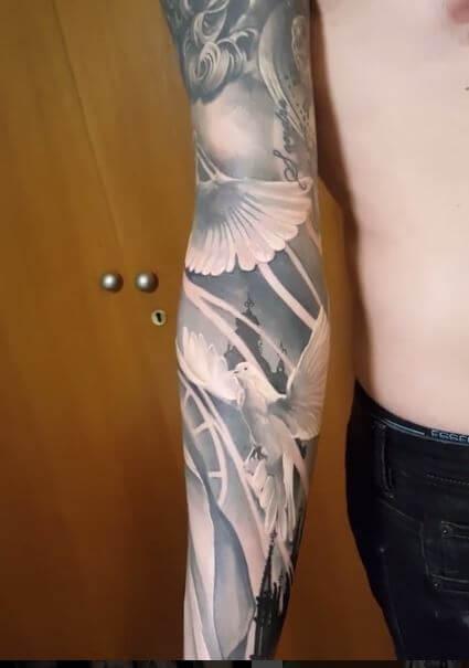 Realismo negro y gris, Christian Kurt Bieber. Tatuaje grande en brazo con motivos religiosos.