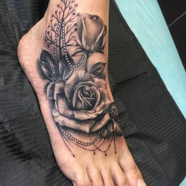 Realismo negro y gris, Joel Federico Bieber. Tatuaje mediano en pie de rosas y collar.