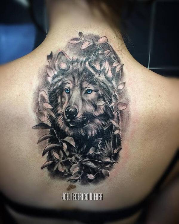 Realismo negro y gris, Joel Federico Bieber. Tatuaje grande en espalda de lobo y plantas.