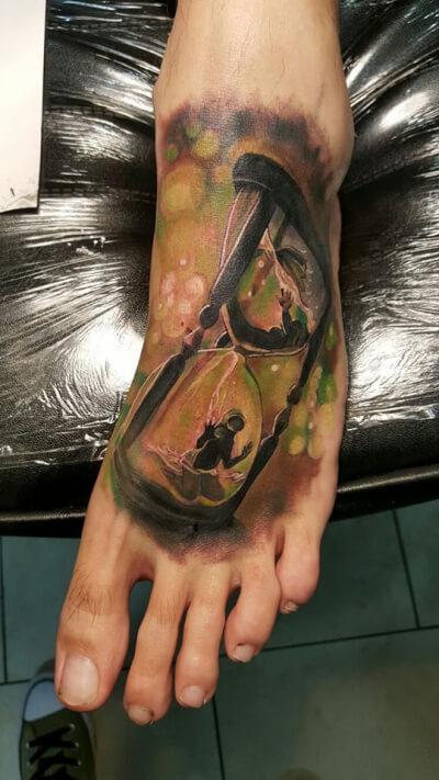 Realismo color, Christian Kurt Bieber. Tatuaje mediano en pie de reloj de arena, sirena y buceador@.