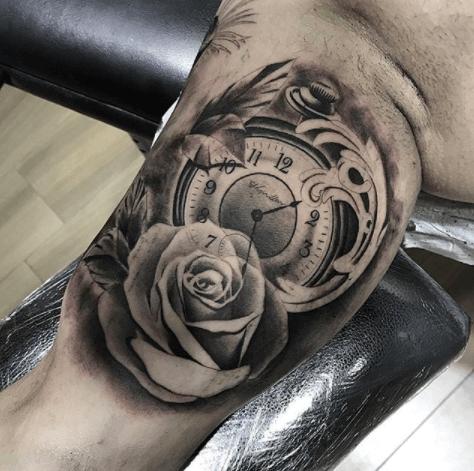 Realismo negro y gris, Héctor Mateos. Tatuaje mediano en brazo de reloj y flor.