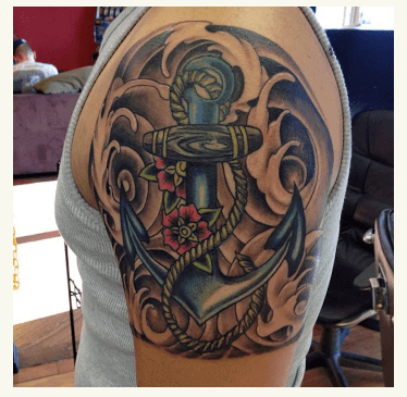 Muchos detalles (olas, cuerda, flores) junto a este ancla tatuada en hombro.